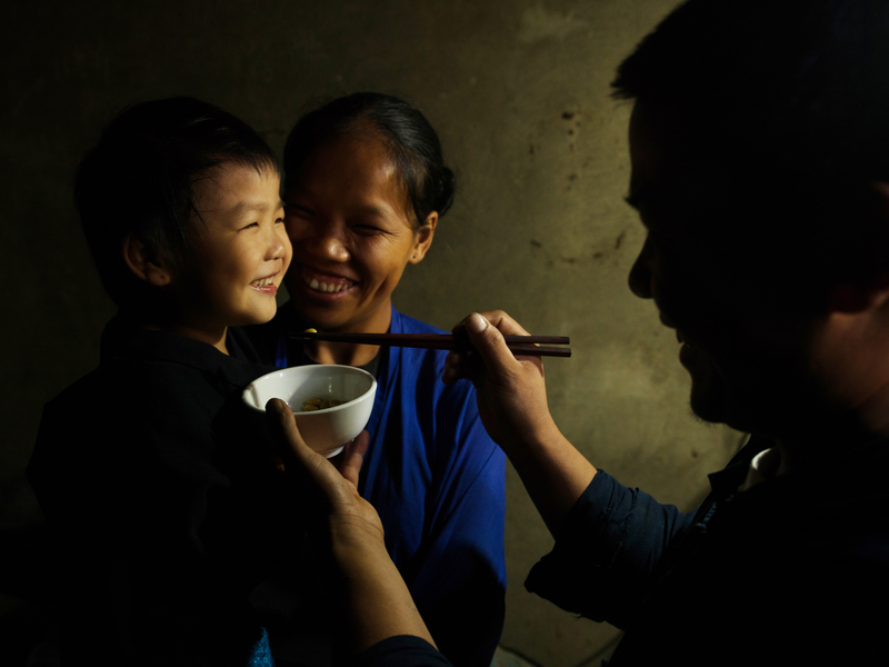 Organic farmer Fu and his wife Feng feed their little girl, in the bowl is a special kind of porridge made of fried rice and tea-oil.