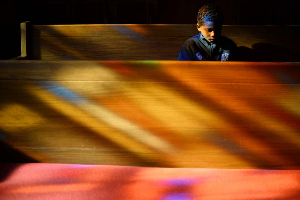 A young boy is illuminated by stained-glass window light during a funeral service for three children killed in a Minneapolis house fire, held by the Spiritual Church of God at the Elim Lutheran Church, Saturday, Oct. 17, 2015, in Robbinsdale, Minn. Authorities say the mother of three children was not home when the blaze started. (Aaron Lavinsky/Star Tribune via AP) MANDATORY CREDIT; ST. PAUL PIONEER PRESS OUT; MAGS OUT; TWIN CITIES LOCAL TELEVISION OUT