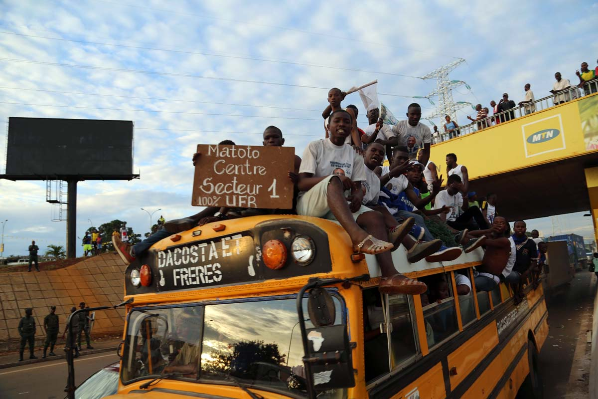 In this photo taken Wednesday, Oct. 7, 2015, supporters of UFR presidential candidate Stadia Toure ride on the back of a bus during a political rally in the city of Conakry, Guinea. Political clashes between the opposition and ruling party in Guinea are setting the stage for the country's second democratic election in more than half a century. The international community watches the West African country, unable to shake the deadly Ebola virus, with concern that ethnic and political tensions brought to the surface in past elections haven't declined in the past five years. (AP Photo/ Youssouf Bah)