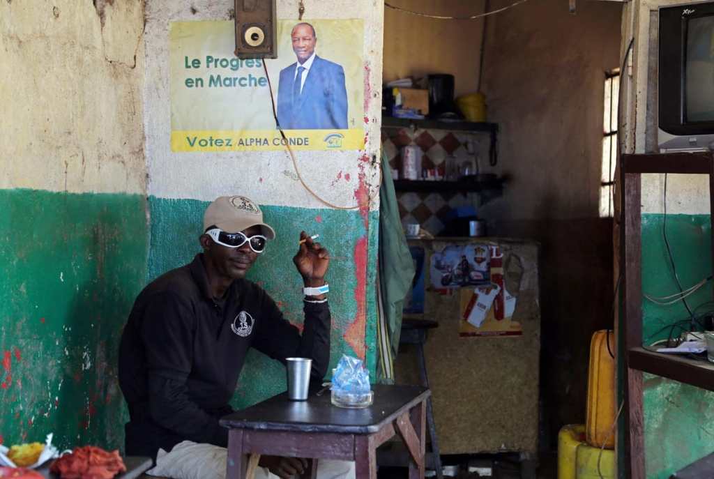 A man sits inside a local restaurant displaying posters of Guinea's incumbent President Alpha Conde, in Conakry, Guinea, Saturday, Oct. 17, 2015, Guinea President Alpha Conde is far ahead of his closest competitor in his bid for re-election and could garner enough support to avoid a runoff, according to preliminary results available Saturday. (AP Photo/Youssouf Bah)