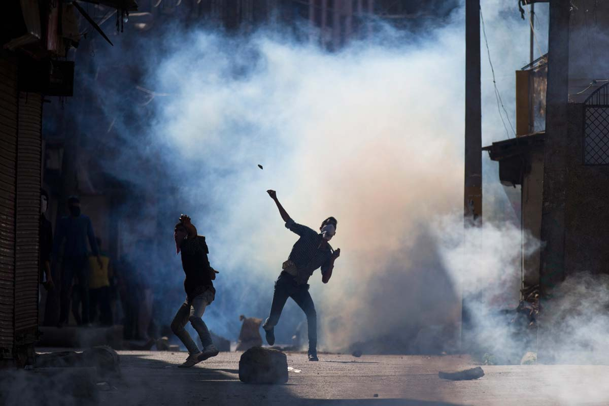 Kashmiri protestors throw stones at Indian security personnel in Srinagar, Indian controlled Kashmir, Friday, Oct. 9, 2015. Police fired teargas and rubber bullets to disperse hundreds of Kashmiris who gathered after Friday afternoon prayers to protest against the arrest of separatist leaders and civilians. They were also protesting against what they said were attempts by the coalition government of the Bharatiya Janata Party and the regional Peoples Democratic Party to divide residents on the basis of religion and choking political space in the restive state. (AP Photo/Dar Yasin)