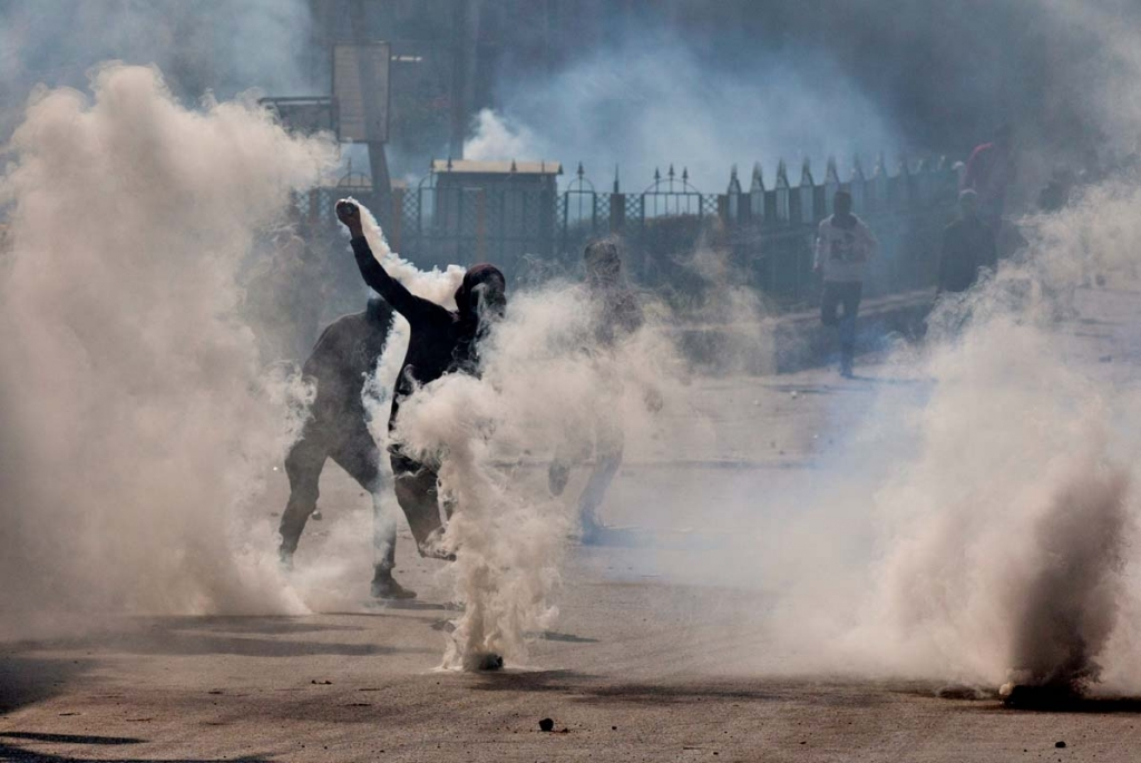 A Kashmiri Muslim protester throws back exploded tear gas shell at Indian security personnel amid tear gas smoke during a protest in Srinagar, Indian controlled Kashmir, Friday, Oct. 16, 2015. Police fired teargas and rubber bullets to disperse Kashmiris who gathered after Friday afternoon prayers to protest against Indian rule in the disputed region. (AP Photo/Dar Yasin)