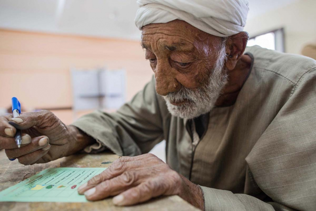Esmail Ahmed , 82 years old, casts his ballot at a polling station during the final day of the first round of parliamentary election, in Fayoum , Egypt, Monday, Oct. 19, 2015. Egyptian authorities have given government workers a half-day off Monday in an attempt to bolster low turnout in the country's parliamentary election. The government has not released turnout figures for voting on Sunday. (AP Photo/Eman Helal)