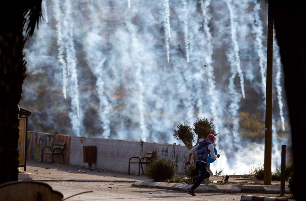 A Palestinian protester runs for cover from tear gas fired by Israeli soldiers during clashes with Israeli troops near Ramallah, West Bank, Saturday, Oct. 17, 2015. Israelis shot dead three Palestinians they said had attacked them with knives on Saturday in Jerusalem and the West Bank city of Hebron, the latest in a month of violent confrontations. (AP Photo/Majdi Mohammed)