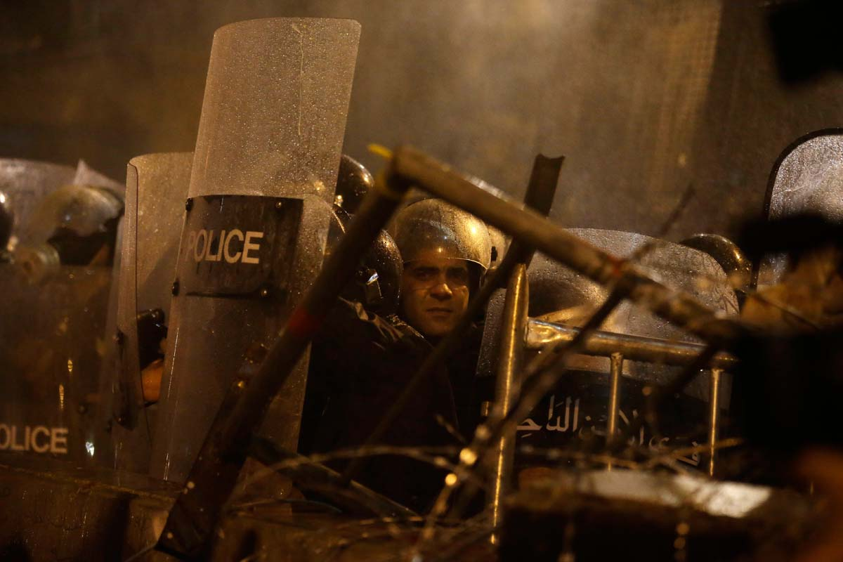 Lebanese riot policemen are seen through the spray of water cannons used against anti-government protesters against the ongoing trash crisis and government corruption, in downtown Beirut, Lebanon, Thursday, Oct. 8, 2015. Lebanese security forces used water cannons and eventually fired tear gas canisters to disperse dozens of anti-government protesters who tried to get past security barricades and reach parliament. (AP Photo/Hassan Ammar)