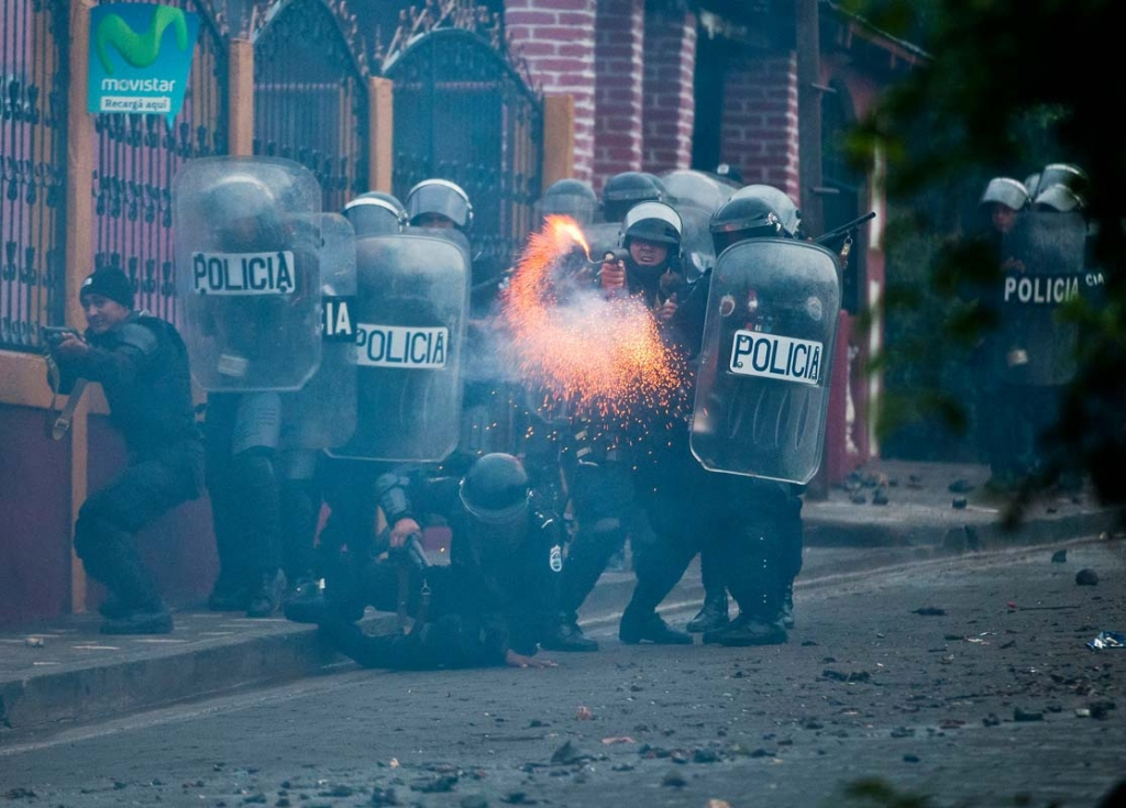 A riot police fires from a homemade mortar during clashes with residents and miners in El Limon, Nicaragua, Saturday, Oct. 17, 2015. Miners have been on strike for weeks after the firing of three union leaders, blocking access to the mine with roadblocks made of rocks and branches, affecting operations. The miners and their families are demanding the Canadian mining company B2Gold rehire the three former workers, saying their dismissals were unjust. By midday Saturday, police has taken control of the mining town. (AP Photo/Esteban Felix)