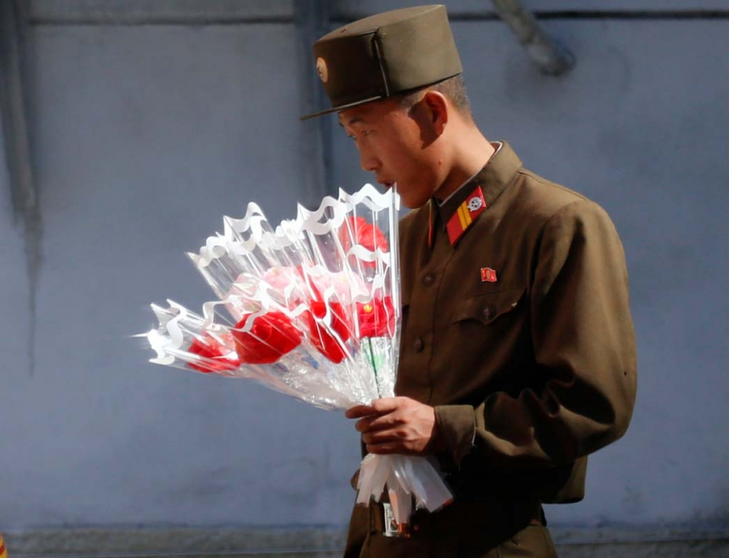 A soldier looks at decorative flowers outside of a shop Friday, Oct. 9, 2015, ahead of Saturday's anniversary celebrations in Pyongyang, North Korea. The country is preparing for the 70th anniversary of the founding of the North Korea Workers' Party on Oct. 10, 2015. (AP Photo/Charles Dharapak)