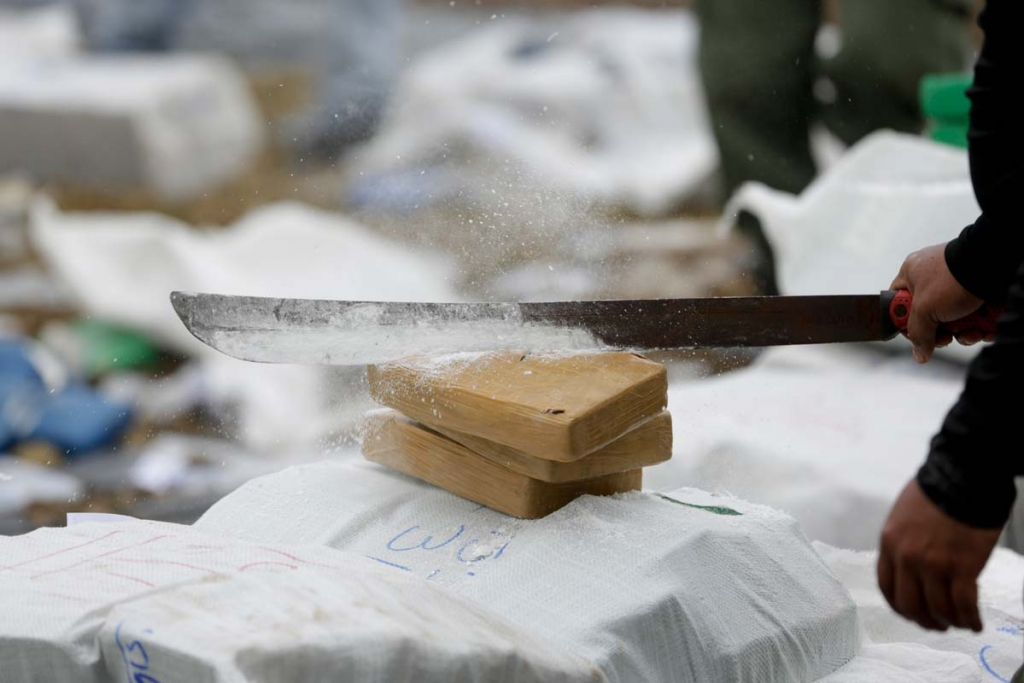 A police officer hacks open packages of cocaine with a machete before they're burned in Panama City, Friday, Oct. 16, 2015. According to National Police, they destroyed at least 10 tons of cocaine, marijuana and heroin seized nationwide over the past month. (AP Photo/Arnulfo Franco)