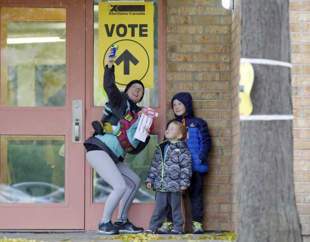 Alexandra Pettit takes a selfie with her kids at the Gloucester Presbyterian Church polling station in Ottawa, after casting her vote in the Canadian federal election on Monday, Oct. 19, 2015. Pivotal elections Monday pitted embattled Prime Minister Stephen Harper against Liberal leader Justin Trudeau, the son of the late Prime Minister Pierre Trudeau. (Patrick Doyle/The Canadian Press via AP)
