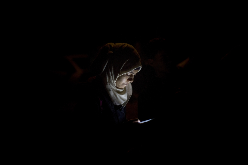 A refugee checks her mobile phone at a resting point shortly after arriving on a dinghy from the Turkish coast to the northeastern Greek island of Lesbos, Tuesday, Oct. 6, 2015. (AP Photo/Santi Palacios)
