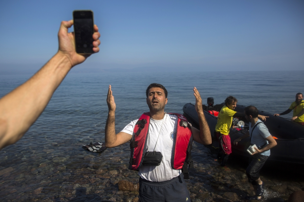 A man prays as another uses his cell phone to take a photograph after their arrival on a dinghy from the Turkish coast to the northeastern Greek island of Lesbos, Monday, Oct. 19, 2015. More than 600,000 people, mostly Syrians, have reached Europe since the beginning of this year. (AP Photo/Santi Palacios)