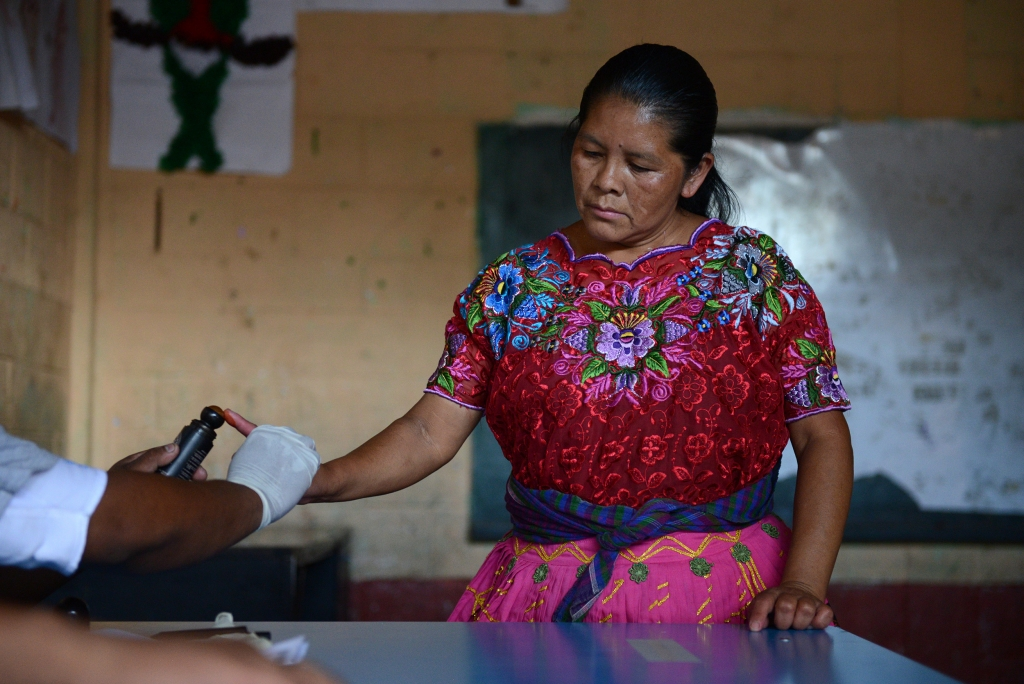 An electoral volunteer marks a woman's finger after she cast her vote in the presidential runoff election, in Chinautla, Guatemala, Sunday, Oct. 25, 2015. Guatemalans are choosing a president amid political upheaval that forced the last elected leader from office. Comedian and political outsider Jimmy Morales is leading in most polls, ahead of former first lady Sandra Torres. (AP Photo/Oliver de Ros)