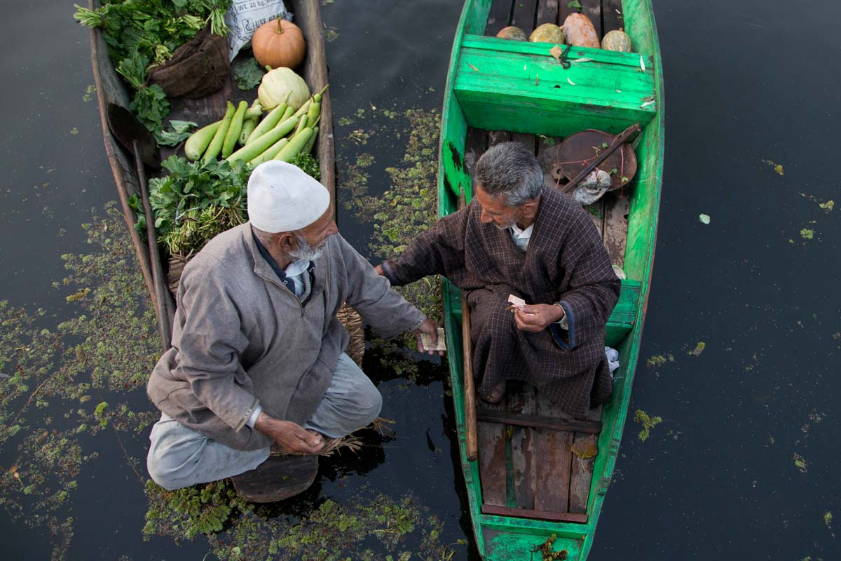 A Kashmiri man, left, negotiates the rate as he prepares to pay money after buying vegetables from a vendor at the floating vegetable market on Dal Lake in Srinagar, Indian controlled Kashmir, Tuesday, Oct. 6, 2015. It's just before dawn when boats laden with fresh produce appear, floating through a maze of waterways on the Dal Lake in Indian Kashmir's main city of Srinagar. In this idyllic setting boatmen haggle over price and vegetables are traded and shifted from one boat to another amid the chirping of birds. (AP Photo/Dar Yasin)