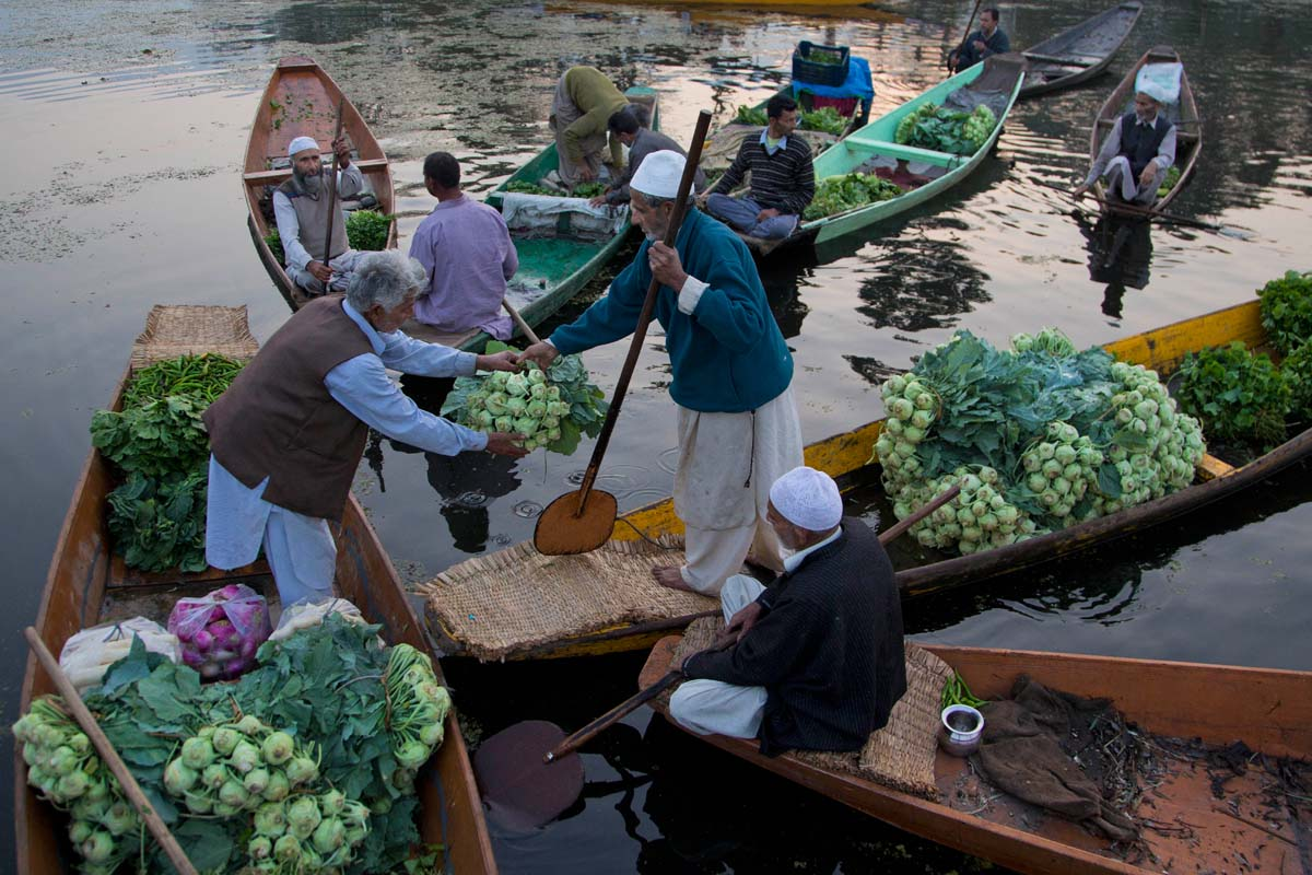 Kashmiri men sell vegetables at the floating vegetable market on Dal lake in Srinagar, Indian controlled Kashmir, Tuesday, Oct. 6, 2015. It's just before dawn when boats laden with fresh produce appear, floating through a maze of waterways on the Dal Lake in Indian Kashmir's main city of Srinagar. In this idyllic setting boatmen haggle over price and vegetables are traded and shifted from one boat to another amid the chirping of birds. (AP Photo/Dar Yasin)