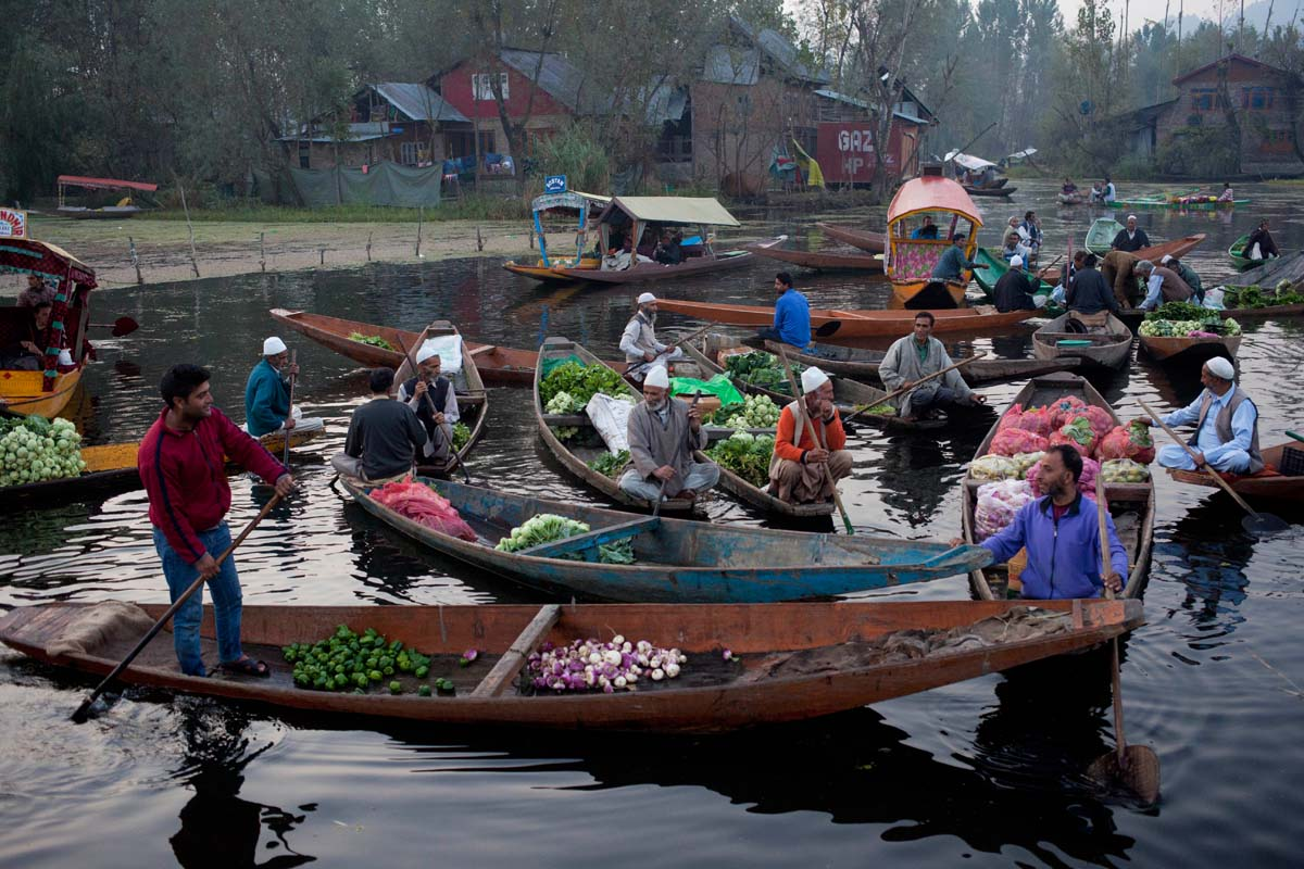 Kashmiri men sell their produce at the floating vegetable market on Dal Lake in Srinagar, Indian controlled Kashmir, Tuesday, Oct. 6, 2015. It's just before dawn when boats laden with fresh produce appear, floating through a maze of waterways on the Dal Lake in Indian Kashmir's main city of Srinagar. This is Kashmir's floating vegetable market, deep inside the lake and surrounded by scenic house boats and water lilies. (AP Photo/Dar Yasin)