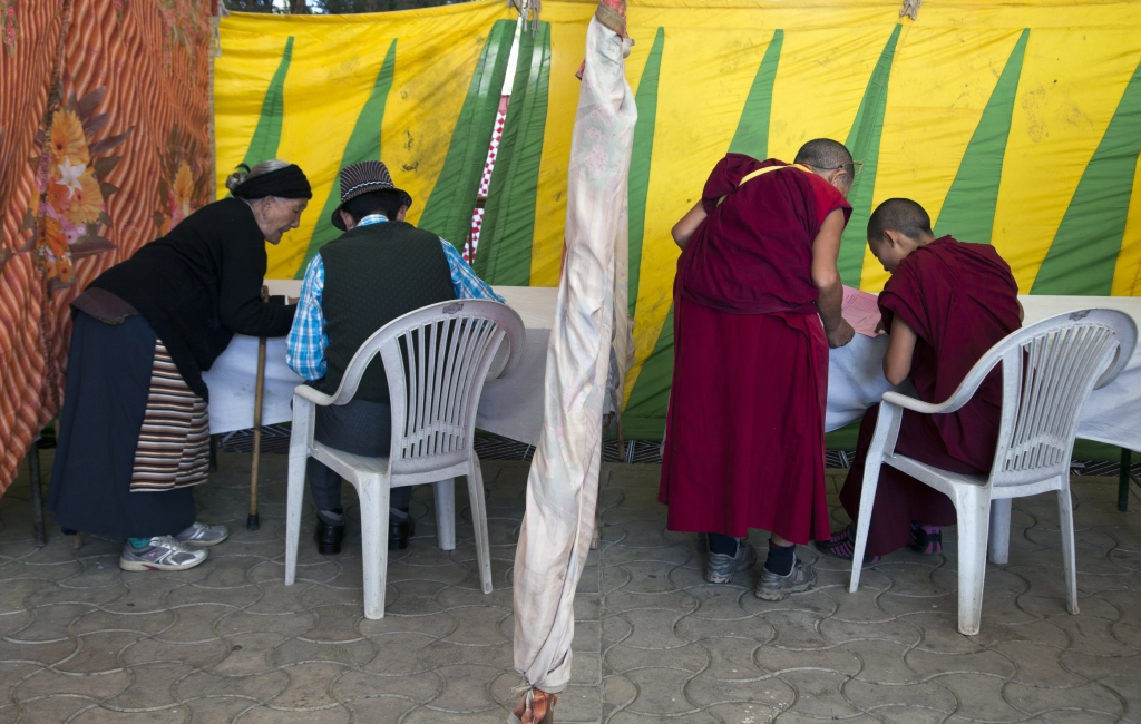 Exile Tibetans write on their ballot papers in make-shift kiosks before casting their votes in the first round of choosing a new government-in-exile in Dharmsala, where the exiled government is based, India, Sunday, Oct. 18, 2015. Tibetan communities worldwide are voting in the first round of choosing a new government-in-exile, and are debating how to carry on their campaign to free their Himalayan homeland from Chinese rule.(AP Photo/Ashwini Bhatia)