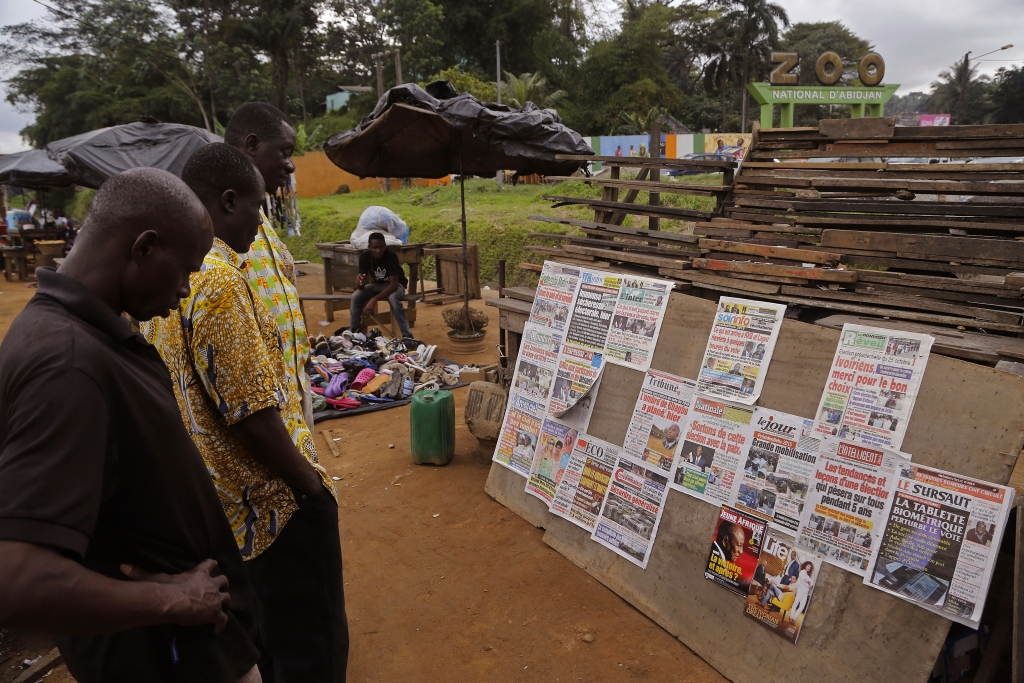 Men read newspaper headlines after recent elections near the entrance to the local zoo, right rear, in Abidjan, Ivory Coast, Monday, Oct. 26, 2015. Ivory Coast voters await result after elections on Sunday as the West African nation held its first presidential election since a disputed vote five years ago. (AP Photo/Schalk van Zuydam)