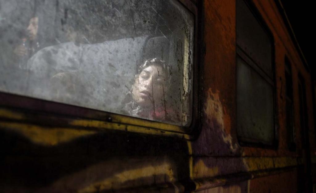 A woman rests aboard a train heading towards Serbia, at the transit camp for refugees near the southern Macedonian town of Gevgelija, early Thursday, Oct. 22, 2015, as migrants make their way across Europe by the tens of thousands, fleeing war or seeking a better life. A U.N. refugee agency field officer says a large number of families with small children have been among the thousands of migrants and it is a tendency seen over the last couple of weeks. (AP Photo/Boris Grdanoski)