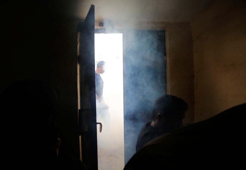 Bahrainis run into a house in an attempt to escape police tear gas and shotgun fire during clashes in the western village of Karzakan, Bahrain, Tuesday, Oct. 20, 2015. Clashes erupted after police began removing street decorations for the Shiite religious occasion of Ashura, a 10-day mourning period for an early Shiite saint. (AP Photo/Hasan Jamali)