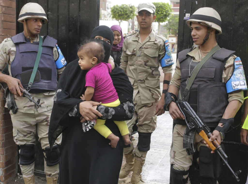 Egyptian soldiers stand guard as a veiled woman voter leaves a polling station of the runoff to the first round of the parliamentary elections in Giza, just outside of Cairo, Egypt, Wednesday, Oct. 28, 2015. (AP Photo/Amr Nabil)