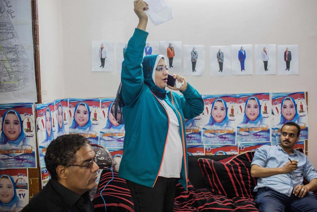 In this Thursday, Oct. 15, 2015 photo, Asmaa Ahmed Abdel Hakeem, an independent candidate, center, makes last-minute preparations at her campaign headquarters in Giza, Egypt, ahead of Egyptian parliamentary elections. The 40 year-old woman is a manager of a family-owned school. It's her first time to run in elections, and says her family has been supportive of the move. (AP Photo/Eman Helal)