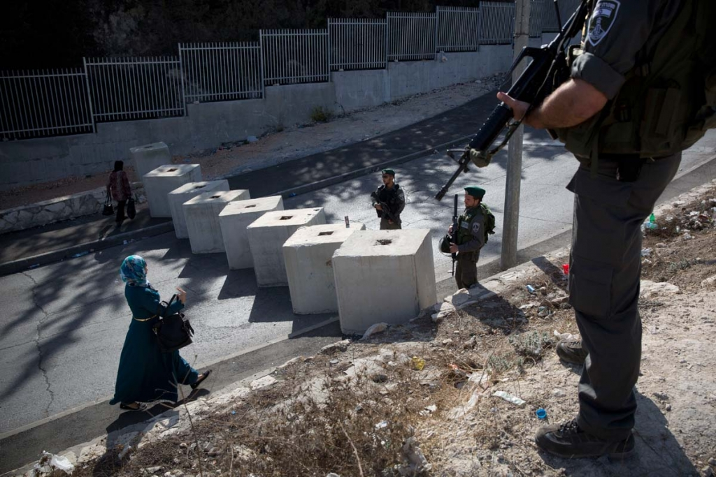 Israeli border police check the ID of a Palestinian woman, next to newly placed concrete blocks in an east Jerusalem neighborhood, Thursday, Oct. 15, 2015. Israel erected checkpoints and deployed several hundred soldiers in the Palestinian areas of the city Wednesday as it stepped up security following a series of attacks in Jerusalem. (AP Photo/Oded Balilty)