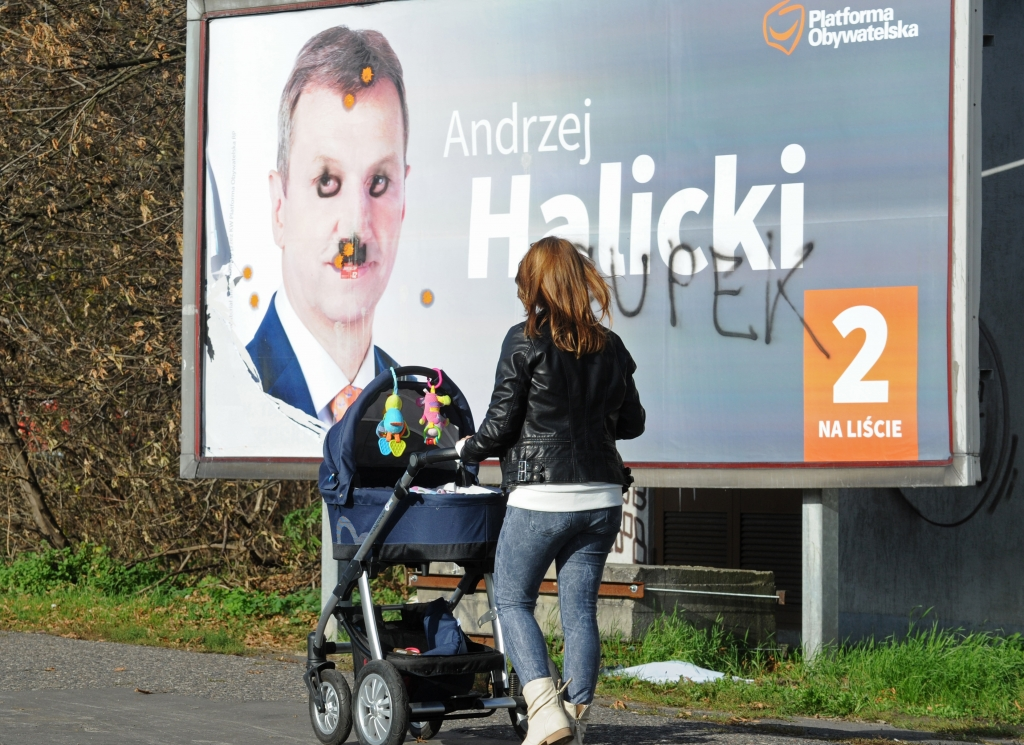 A woman walks past a damaged Civic Platform election poster in Warsaw, Poland, Monday, Oct. 26, 2015. According to an exit poll following the Sunday elections and released early Monday, the conservative Law and Justice won 37.7 percent of the votes, trouncing the governing pro-business Civic Platform, which took 23.6 percent. (AP Photo/Alik Keplicz)