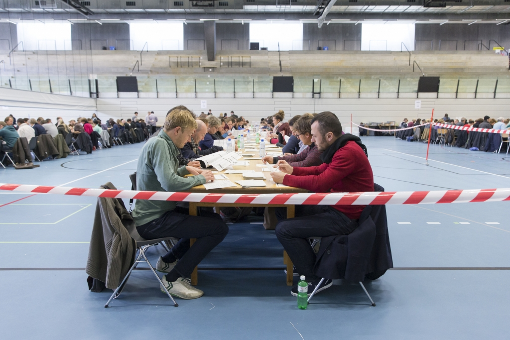 Helpers count ballot papers at a gymnasium in Bern, Switzerland, Sunday, Oct. 18, 2015. Swiss voters have cast ballots to elect their parliament and polls show a nationalist party could advance amid widespread concerns about the recent influx of migrants into Europe. (Peter Klaunzer/Keystone via AP)