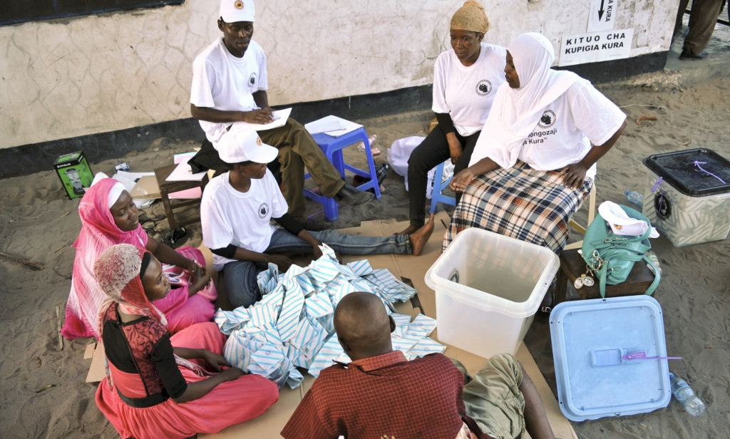 Officials from the electoral commission, watched by representatives of political parties, start the vote-counting process at a polling station in the Temeke district of Dar es Salaam, Tanzania Sunday, Oct. 25, 2015. Voting has taken place in Tanzania's general elections in which the ruling party faces a strong challenge from a united opposition, with the ruling party's candidate John Magufuli battling former Prime Minister Edward Lowassa, who defected to the opposition earlier this year after being rejected as the ruling party's candidate. (AP Photo/Khalfan Said)