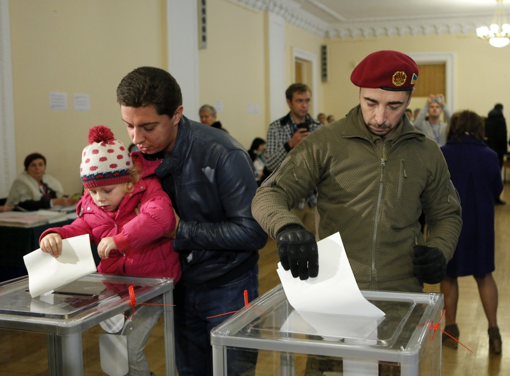 A Ukrainian voter in uniform casts his ballot at a polling station in Kiev, Ukraine, Sunday, Oct. 25, 2015. Polling stations opened in Ukraine on Sunday for regional and local elections across the country, except for the separatist-held regions in the east. (AP Photo/Sergei Chuzavkov)