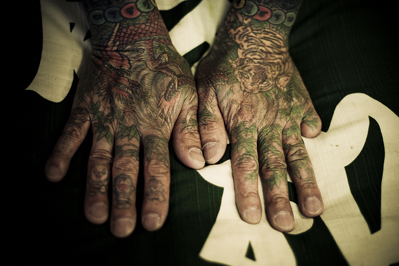 Tattooed hands with a digit missing. A traditional Japanese tattoo, as used often by the Yakuza, Is a very old and time-consuming process of manually sticking a stick with at the point several sharp inked needles in the skin. This has to happen at a precise angle (depending on skin thickness) and at a precise speed (120/minute), and this is a skill that only traditional Japanese tattoo masters possess. The result is an intricacy, a color palette and a pattern which is not possible with the modern way of tattooing with a machine.Master Tattooist Hori Sensei invites you, he does not accept regular clients. With him, completing a traditional Japanese tattoo takes about 100 hours, can cost up to $10,000, and a schedule of daily or weekly visits needs to be made. As a client, you have only a little say in the design of the tattoo. Hori Sensei determines what is best for you after taking time to talk to you and to get to know you. Only a few traditional Japanese tattoo experts are still alive today in Japan. - 2009
