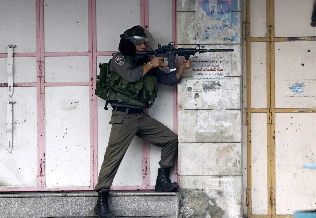 epa04970663 An Israeli border policeman aims his weapon towards Palestinian protesters during clashes in the West Bank city of Hebron, 09 October 2015. Israeli soldiers killed four Palestinians in clashes on the border with the Gaza Strip, while there were four stabbing incidents inside Israel targeting both Jews and Palestinians. Violence has been ongoing for weeks, focused on Jerusalem and nearby areas on the West Bank amid rising concerns the situation could lead to an even greater escalation if not scaled back soon. EPA/ABED AL HASHLAMOUN