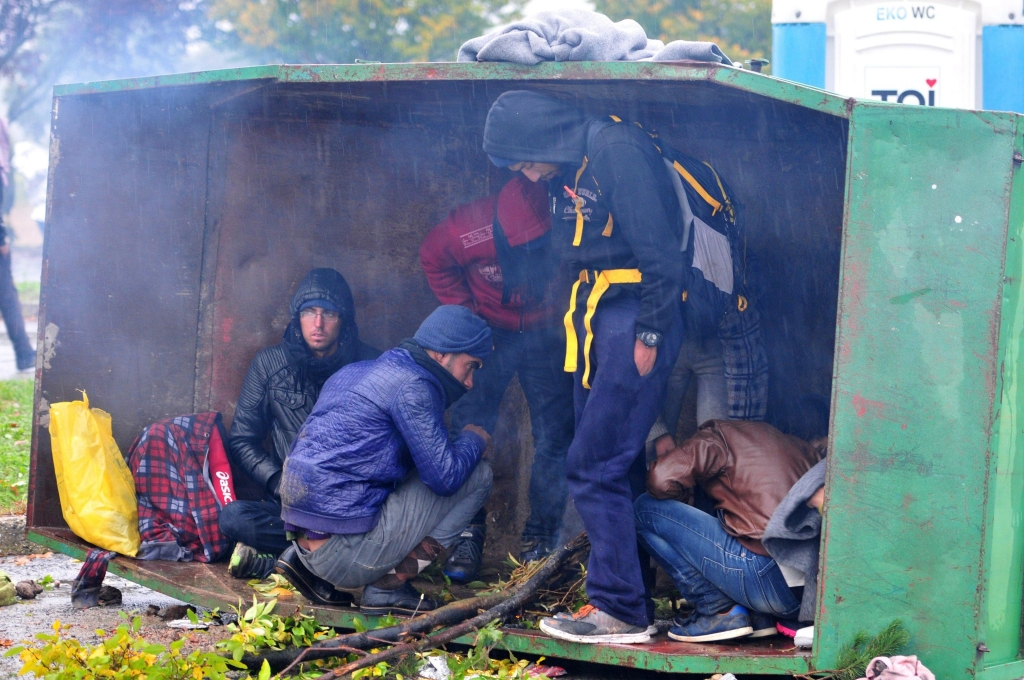 epa04983755 Migrants seek shelter in a container as they wait in the rain in Trnovec, due to the Slovenia border crossing closure in Croatia, 19 October 2015. Many of the migrants are exhausted, some asleep on the hard asphalt. They have been waiting for hours in the hope of entering Slovenia, the next stage on their long journey to Austria, Germany or Sweden.  EPA/IGOR KUPLJENIK