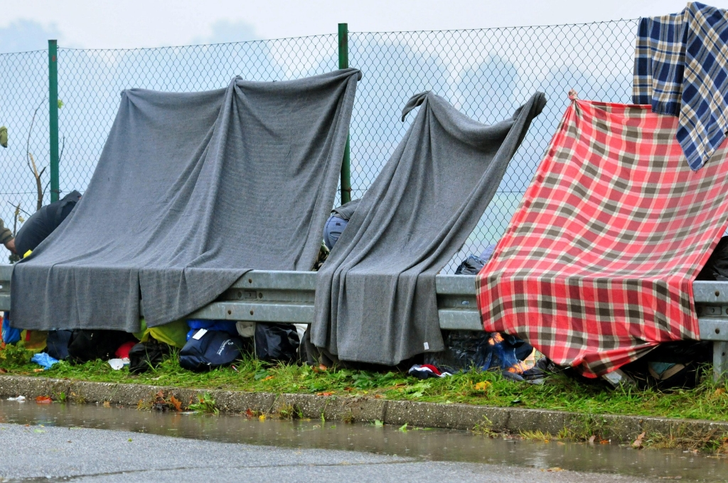 epa04983624 Migrants seek shelter under blankets attached to a fence as they wait in the rain at the closed Croatian-Slovenian border crossing in Trnovec, Croatia, 19 October 2015. They have been waiting for hours in the hope of entering Slovenia, the next stage on their long journey to Austria, Germany or Sweden. Slovenia had deployed its military to its border with Croatia to help police handle the influx of refugees who re-routed their course across the Balkans after Hungary refused to let them through.  EPA/IGOR KUPLJENIK