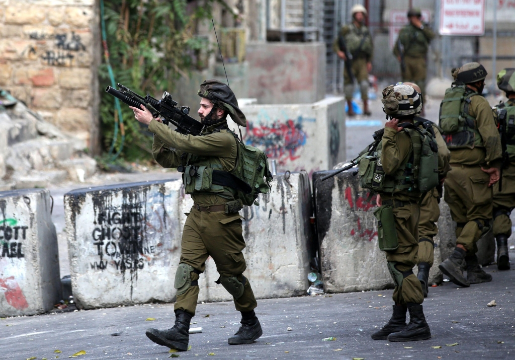 epa04984192 Israeli soldiers take up position during clashes with Palestinian protesters in the West Bank city of Hebron, 19 October 2015. Israel wants to partially wall off and place obstacles in Arab sections of Jerusalem to hinder Palestinian access to predominantly Jewish areas after a wave of knife attacks. Israel's existing security wall, built in 2002, was built between East Jerusalem and the West Bank, outside the Israeli-drawn municipal boundary. EPA/ABED AL HASHLAMOUN