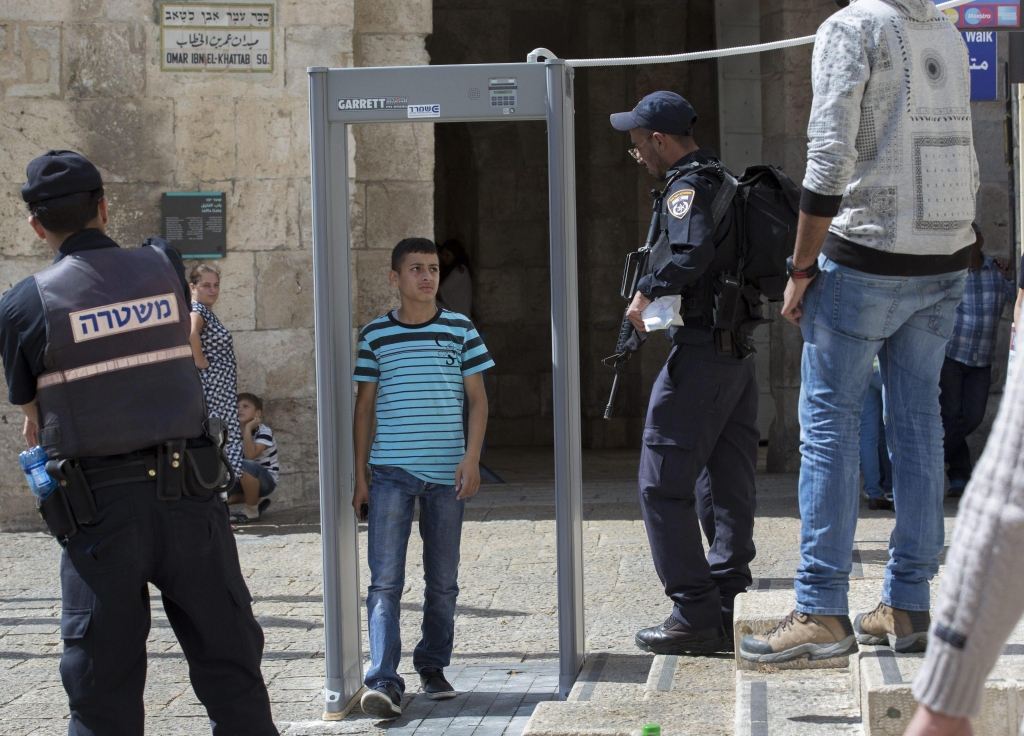 epa04968882 An Israeli policeman makes a young Palestinian man walk through a newly-installed metal detector just inside Jerusalem's Old City walls at the Jaffa Gate, 08 October 2015. The teenager then had his ID checked before he was allowed to leave the Old City for Jerusalem proper. Israel is increasing security again in Jerusalem's Old City as the current wave of violence continues where a Palestinian stabbed four Israelis the same day in Tel Aviv. In a bid to calm tempers after days of violence, Israeli Prime Minister Benjamin Netanyahu ordered politicians not to visit a sensitive holy site in Jerusalem. EPA/JIM HOLLANDER