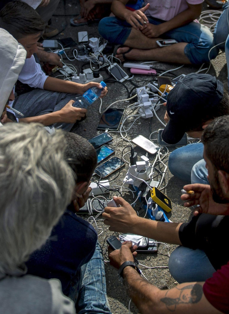 epa04933285 Refugees charge their mobile phones at the border station between Serbia and Hungary near Horgos, northern Serbia, 16 September 2015. Hungarian police fire tear gas and deploy water cannon to push migrants away from a barricade at Roszke on the border with Serbia. Hungary declared a state of emergency in two counties along its border with Serbia, after it used a boxcar fitted with razor wire to block a major entry point there. Declaring the state of emergency paves the way for parliament to allow the army to reinforce police along the border, as new measures to crackdown on refugees go into effect. EPA/TAMAS SOKI HUNGARY OUT
