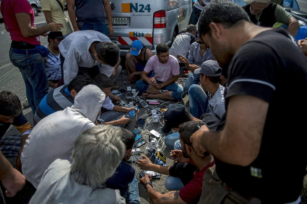 epa04933278 Refugees charge their mobile phones at the border station between Serbia and Hungary near Horgos, northern Serbia, 16 September 2015. Hungarian police fire tear gas and deploy water cannon to push migrants away from a barricade at Roszke on the border with Serbia. Hungary declared a state of emergency in two counties along its border with Serbia, after it used a boxcar fitted with razor wire to block a major entry point there. Declaring the state of emergency paves the way for parliament to allow the army to reinforce police along the border, as new measures to crackdown on refugees go into effect. EPA/TAMAS SOKI HUNGARY OUT