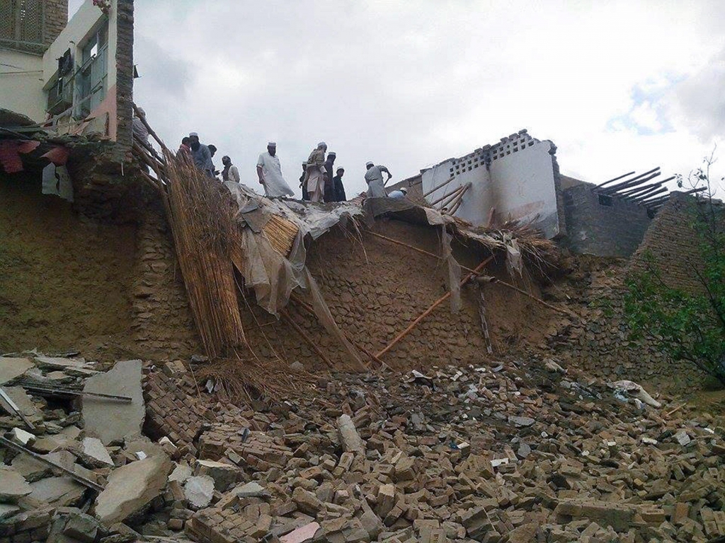 epa04997032 Pakistanis survey houses that collapsed following a 7.7 magnitude earthquake, in the Khyber Agency near the Afghan border, Pakistan, 26 October 2015. A strong earthquake with a magnitude of 7.7 hit northern Afghanistan's Hindu Kush mountain range causing damage in Pakistan and India. At least 90 people are believed to have been killed, mostly in the Peshawar region of Pakistan, 20 in Afghanistan and hundreds wounded. Tremors were felt in northern India, including the capital New Delhi, causing thousands of people to evacuate buildings. Authorities also closed the underground train system.  EPA/WALI KHAN SHINWARI