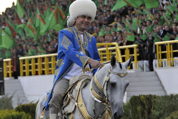 """FILE - Turkmenistan's President Gurbanguli Berdymukhamedov smiles as he rides a horse with a dove on his shoulder an a ceremony in the capital Ashgabat, Turkmenistan, in this Sunday, April 24, 2011 file photo. A series of public shows and sports events will be held during the first week of April to mark the """"era of power and happiness"""" recently announced by Berdymukhamedov, state newspaper Neutral Turkmenistan reported Friday March 30 2012. The week has now been dubbed the """"Week of Health and Happiness"""" and will among other things see the staging of plays called """"The Inspirational Era of Happiness"""" and """"The Era of Power is Illuminated by Happiness."""" (AP Photo/Alexander Vershinin, File)"""