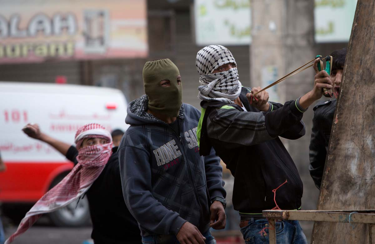 A Palestinian protester uses a slingshot during clashes with Israeli soldiers following a funeral of Ibrahim Skafi, 22, in the West Bank city of Hebron, Thursday, Nov. 5, 2015. Skafi rammed his vehicle into an Israeli police officer in the West Bank on Wednesday, seriously injuring the officer before he was shot and killed, police said. (AP Photo/Majdi Mohammed)