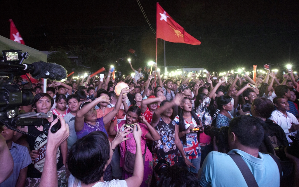 Supporters of Myanmar opposition leader Aung San Suu Kyi's National League for Democracy party cheer as they watch the result of general election on an LED screen outside the party's headquarters Sunday, Nov. 8, 2015 in Yangon, Myanmar. Millions of citizens voted Sunday in Myanmar's historic general election that will test whether the military's long-standing grip on power can be loosened, with opposition leader Suu Kyi's party expected to secure an easy victory. (AP Photo/Khin Maung Win)