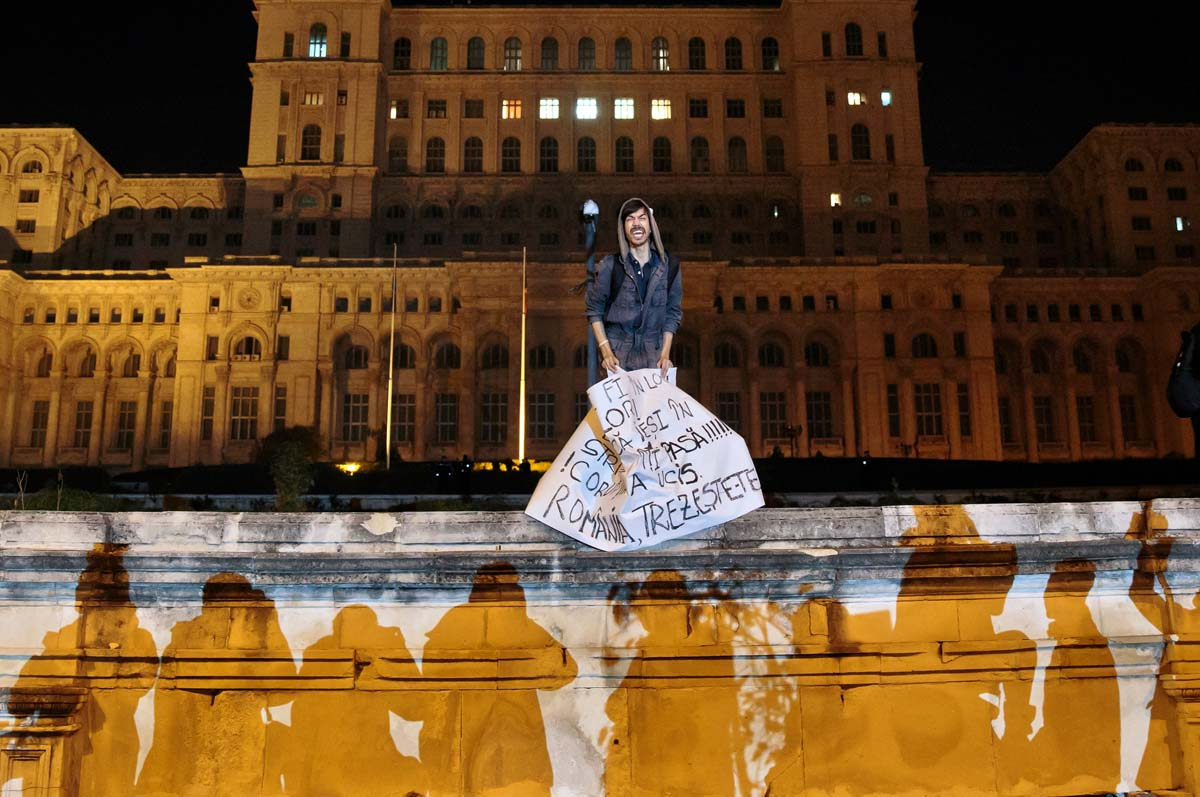 """A protester screams holding a paper that reads """"Corruption has killed - Romania wake up"""" back-dropped by the communist era built House of the People, now housing the Romanian parliament during a rally joined by thirty-five thousand people, according to local media quoting the Romanian Gendarmerie, calling for early elections, in Bucharest, Romania, Wednesday, Nov. 4, 2015. Prime Minister Victor Ponta announced the resignation of his government Wednesday following huge protests the day before in the wake of a nightclub fire that killed more than 30 people.(AP Photo/Vadim Ghirda)"""