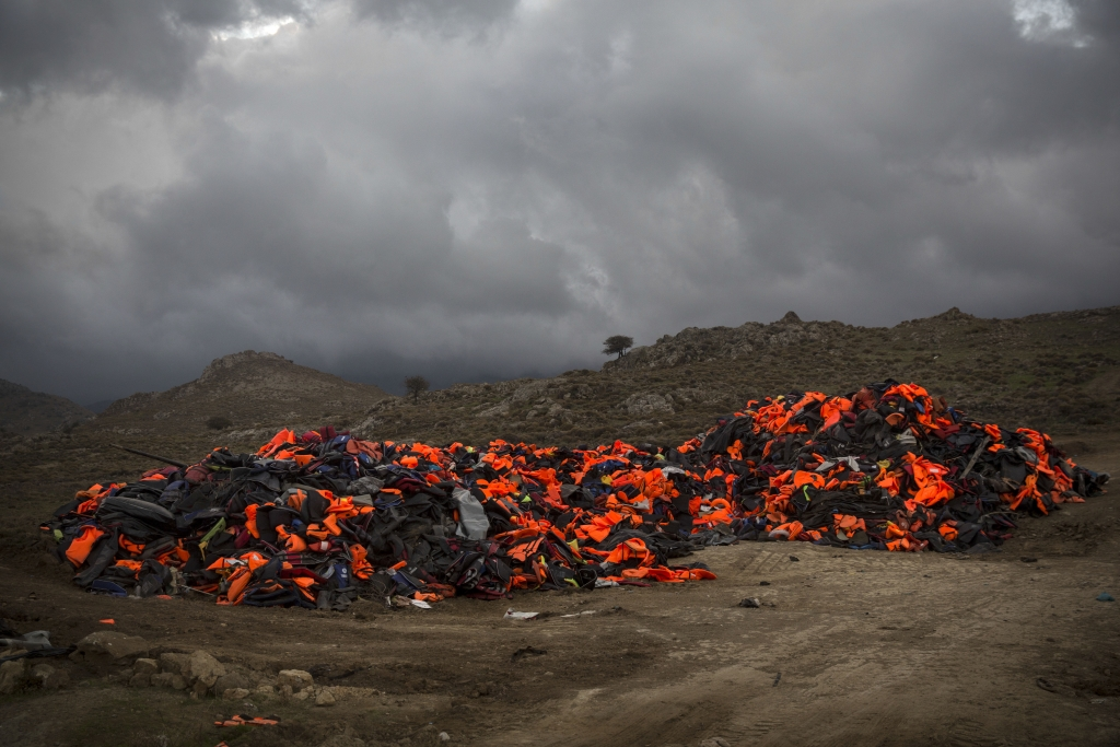 Piles of life jackets used by refugees and migrants to cross the Aegean sea from the Turkish coast remain stacked on the Greek eastern island of Lesbos, on Sunday, Nov. 22, 2015. Greek authorities have started supplementary identity checks on immigrants reaching Athens by ferry from the country's eastern islands, after breaking up a ring that sold fake identity documents to migrants arriving on Lesbos. (AP Photo/Santi Palacios)