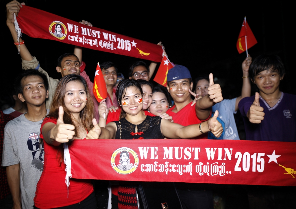 Supporters of Myanmar opposition leader Aung San Suu Kyi's National League for Democracy party show thumbs-up signs as they watch the result of general election on an LED screen displaying outside the party's headquarters Sunday, Nov. 8, 2015 in Yangon, Myanmar. Millions of citizens voted Sunday in Myanmar's historic general election that will test whether the military's long-standing grip on power can be loosened, with opposition leader Suu Kyi's party expected to secure an easy victory. (AP Photo/Khin Maung Win)