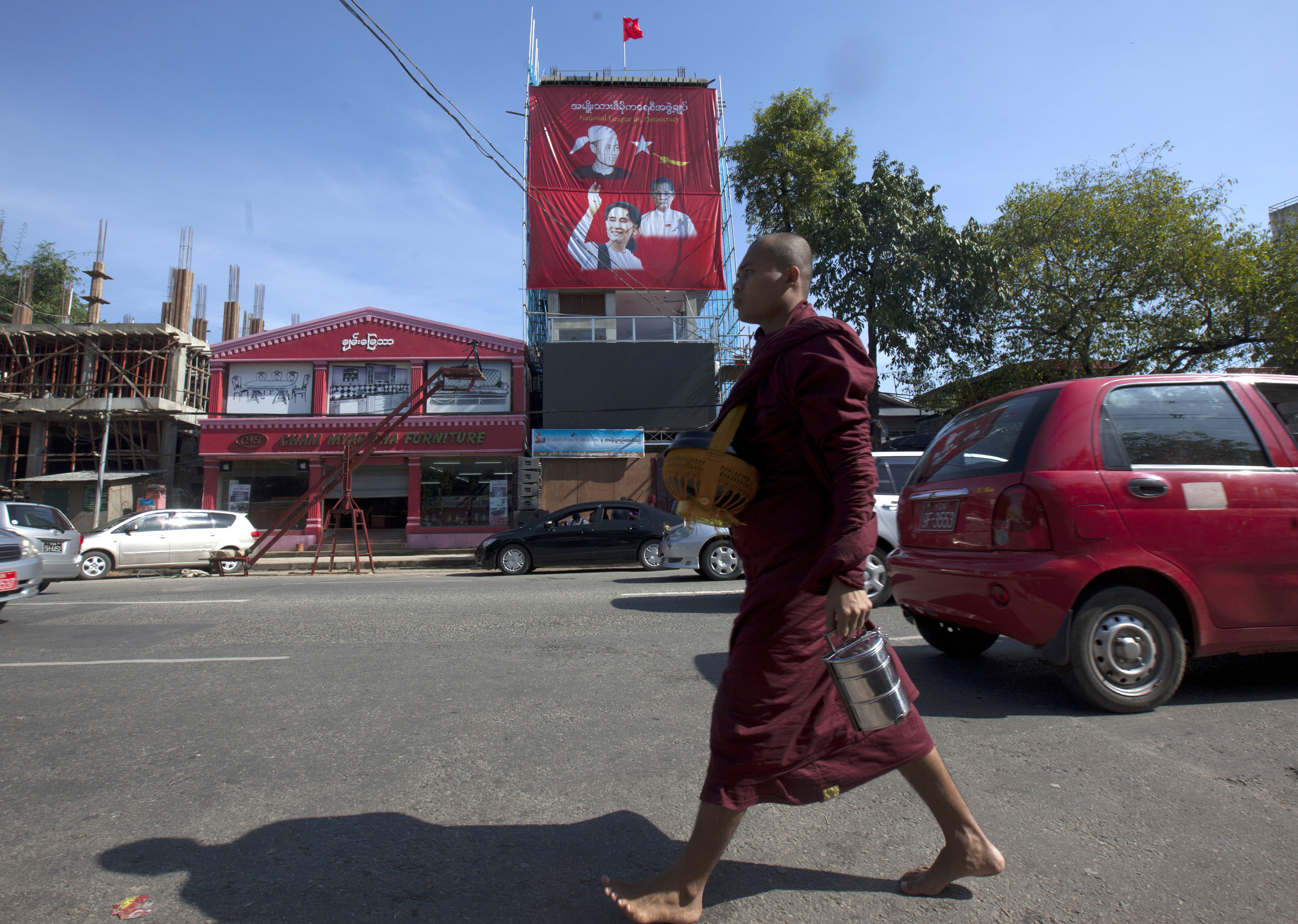 A Buddhist monk walks on a road near the headquarters of Myanmar opposition leader Aung San Suu Kyi's National League for Democracy party while collecting morning alms Monday, Nov. 9, 2015, in Yangon, Myanmar. (AP Photo/Khin Maung Win)