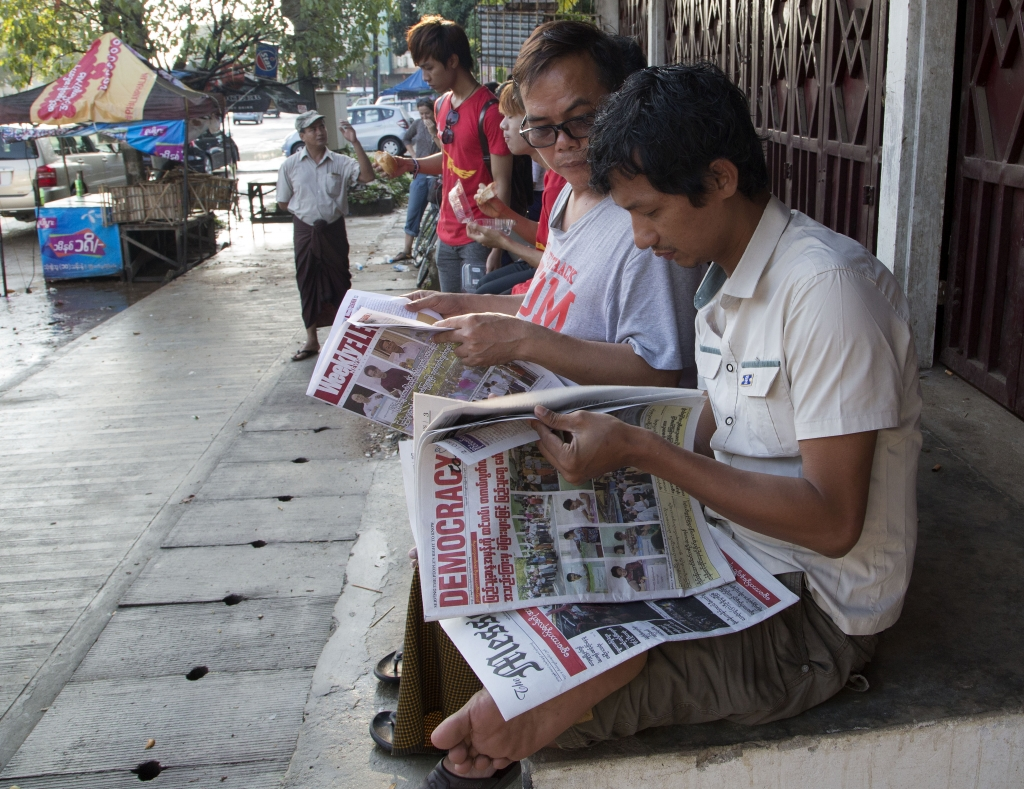 Locals read morning newspapers outside the headquarters of Myanmar's National League for Democracy party in Yangon, Myanmar, Monday, Nov. 9, 2015. With tremendous excitement and hope, millions of citizens voted Sunday, Nov. 8 in Myanmar's historic general election that will test whether the military's long-standing grip on power can be loosened, with opposition leader Aung San Suu Kyi's party expected to secure an easy victory. (AP Photo/Mark Baker)