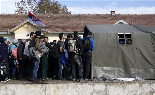 Migrants waiting to board a train at the train station in Sid, about 100 km west from Belgrade, Serbia, Wednesday, Nov. 11, 2015. Slovenia on Wednesday began erecting a razor-wire fence along its border with Croatia to control the influx of migrants, as European and African leaders gathered in Malta to seek long-term solutions to the flow of people making their way across Europe. (AP Photo/Darko Vojinovic)