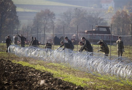 Slovenian soldiers erect a razor-wired fence on the Croatian border in Gibina, Slovenia, Wednesday, Nov. 11, 2015. Slovenia has started erecting a barbed-wire fence on the border with Croatia to prevent uncontrolled entry of migrants into the already overwhelmed alpine state. (AP Photo/Darko Bandic)