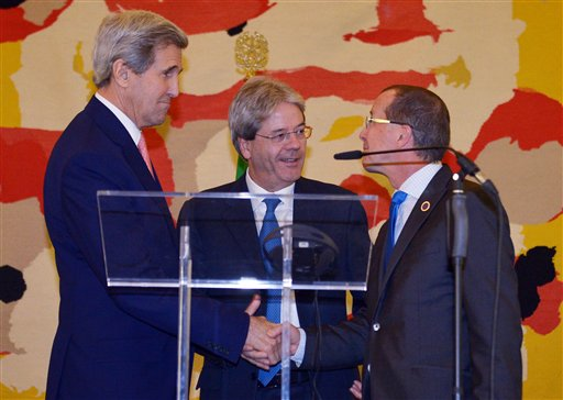 US Secretary of State John Kerry, left, Italian Foreign Minister Paolo Gentiloni, centre, and UN special envoy for Libya Martin Kobler shake hands after their press conference,  following an international conference on Libya at the Ministry of Foreign Affairs in Rome, Sunday, Dec. 13, 2015. Foreign ministers were poised to endorse a U.N.-brokered national unity plan for Libya at a Rome conference aimed at prodding the North Africa country's bickering factions to fulfill their commitment to sign the agreement and abide by its terms. (Mandel Ngan/Pool Photo via AP)
